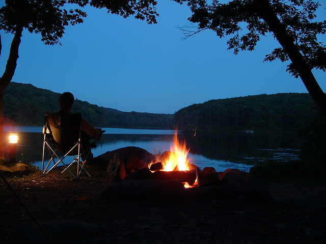 sitting by campfire and water